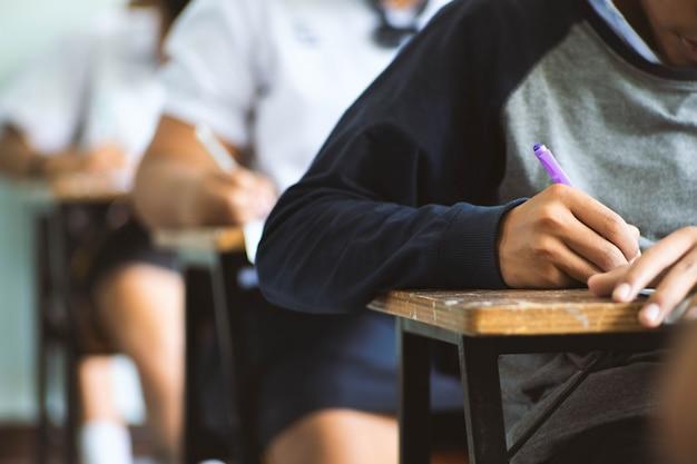 Die studenten, die in der hand stift tun prüfungen schreiben, beantworten blattübungen im klassenzimmer mit druck. Premium Fotos
