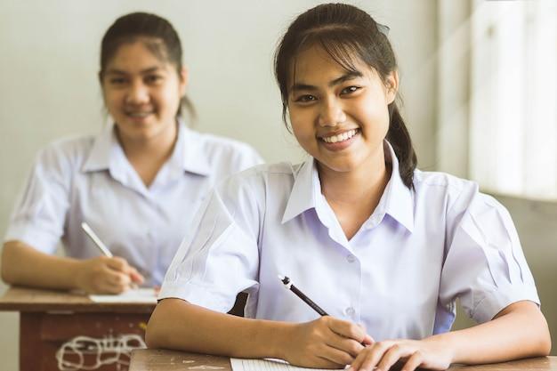 Die studenten, die in der hand stift tun prüfungen schreiben, beantworten blattübungen im klassenzimmer mit lächeln und glücklich. Premium Fotos