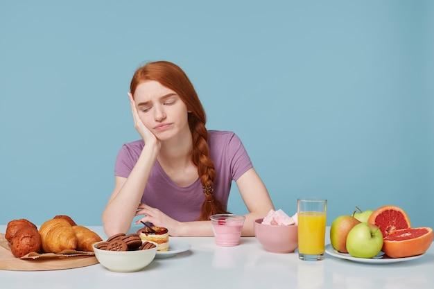 Die studioaufnahme eines rothaarigen mädchens, das mit unzufriedener traurigkeit auf backwaren schaut, denkt darüber nach, was zu essen ist Kostenlose Fotos