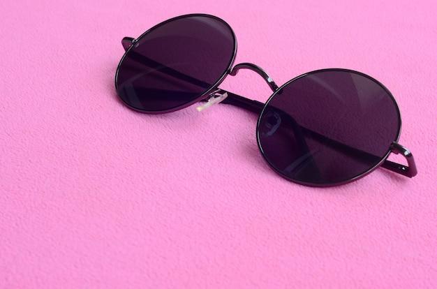 Die stylische schwarze sonnenbrille mit runder brille liegt auf einer decke aus weichem und flauschigem hellrosa fleece Premium Fotos