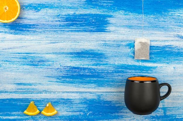 Die tasse tee auf einem blauen hintergrund. teebeutel und orangenscheiben Premium Fotos