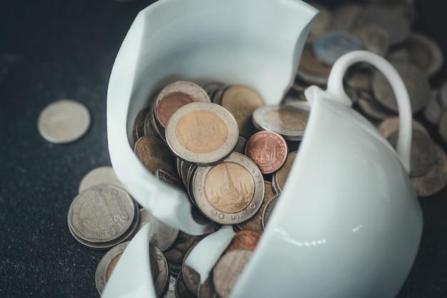 Die tasse wurde gerade in stücke zerbrochen und münzen liegen verstreut herum Premium Fotos