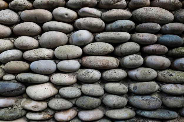 Die textur der steinmauer, mauerwerk aus natürlichen ovalen steinen. Premium Fotos