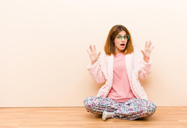 Die tragenden pyjamas der jungen frau, die zu hause sitzen, fühlen sich betäubt und erschrocken und fürchten etwas, das erschreckend ist, wenn die hände offenes vorderes sprichwort öffnen, bleiben weg Premium Fotos