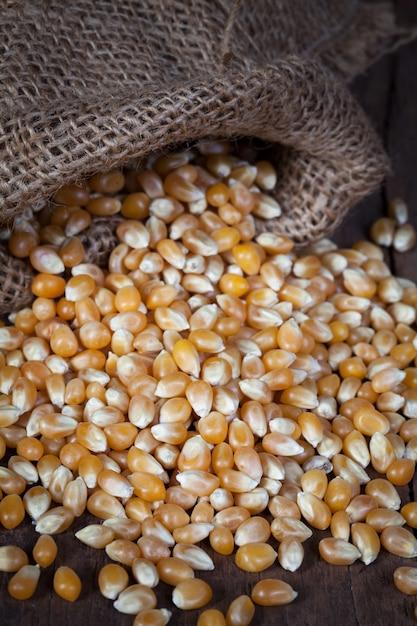 Die trockenen maiskörner werden aus dem hanfsack auf den holztisch gegossen. Premium Fotos