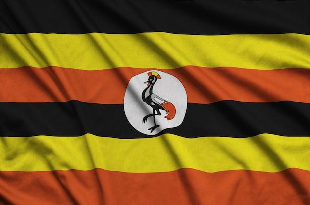Die uganda-flagge ist auf einem sportstoff mit vielen falten abgebildet. Premium Fotos
