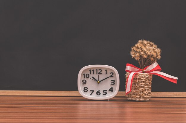 Die uhr und der blumentopf stehen auf dem tisch. Premium Fotos
