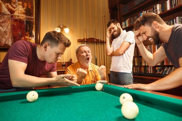 Die unzufriedenen männer spielen nach der arbeit im büro oder zu hause billard. Kostenlose Fotos