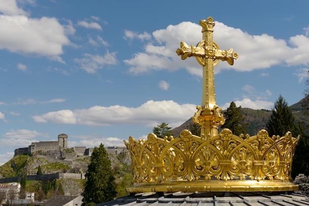 Die vergoldete krone und das kreuz in lourdes Premium Fotos