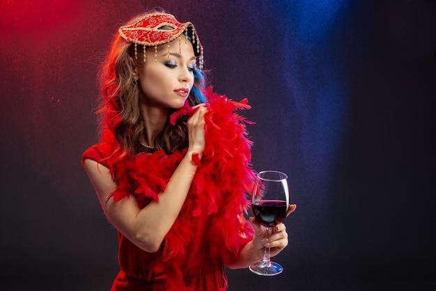 Die verlockende frau im roten abendkleid, die ein glas wein hält, richtet die boa auf ihren schultern gerade Premium Fotos
