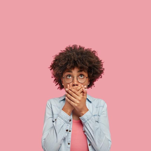 Die vertikale einstellung einer überraschten afroamerikanerin bedeckt den mund mit beiden händen, versucht sprachlos zu sein, schaut mit geschocktem ausdruck nach oben und bemerkt etwas seltsames, das über einer rosa leeren wand isoliert ist Kostenlose Fotos