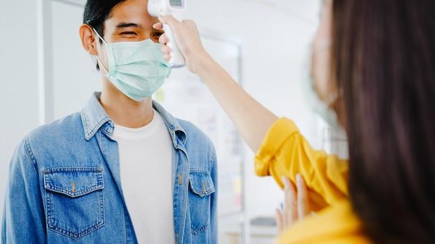 Die weibliche empfangsdame in asien, die eine tragende gesichtsmaske trägt, verwendet vor dem betreten des büros einen infrarot-thermometerprüfer oder eine temperaturpistole auf der stirn des kunden. lebensstil neu normal nach koronavirus. Kostenlose Fotos