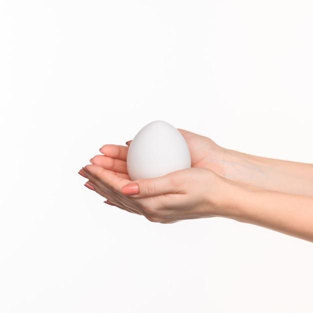 Die weiblichen hände halten ein weißes ei auf weiß. Kostenlose Fotos