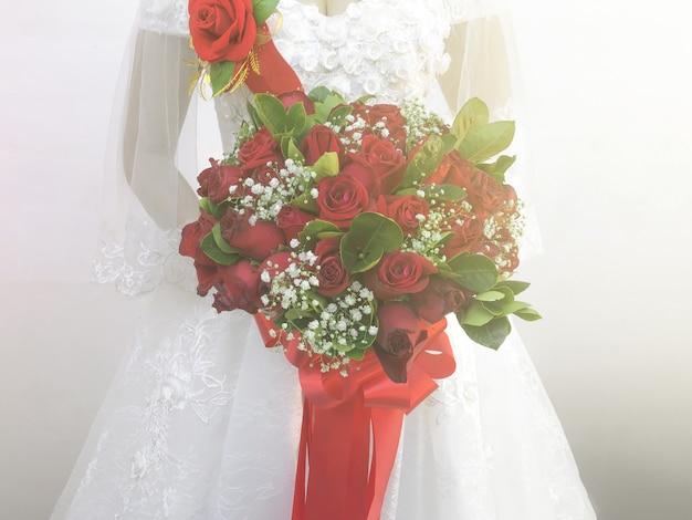 Die weiße kleiderbraut, die rosenblumenstrauß mit heller wand als hintergrund hält. Premium Fotos