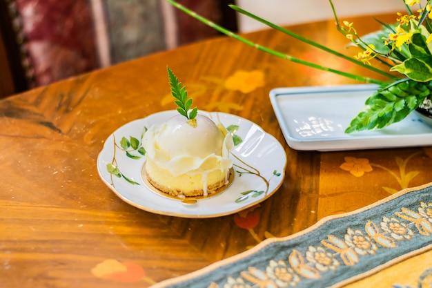 Die weiße schokolade, die mit beerenkuchen sortiert wurde, diente in einer weißen platte auf der luxustischdecke und dem holztisch Premium Fotos
