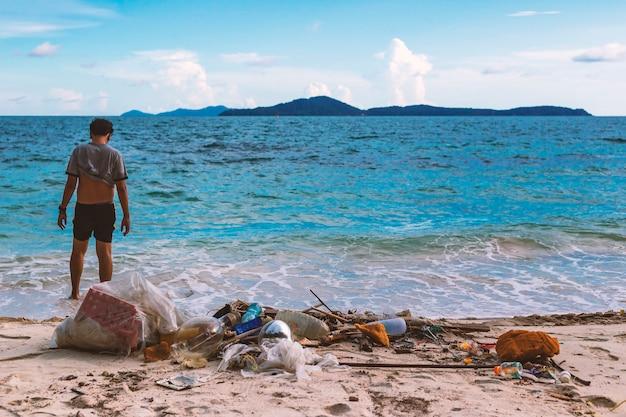 Die zerstörung der natur durch die hand des menschen. vom hausmüll ins meer geworfen. Premium Fotos