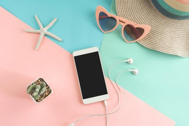 Die zubehörartikel der frauen mit intelligentem telefon auf pastellfarbhintergrund, sommerferienkonzept Premium Fotos
