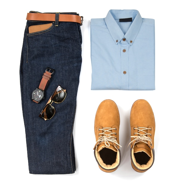Die zufälligen ausstattungen der männer für mannkleidung mit dem blauen hemd, blue jeans, gurt, uhr, sonnenbrille und gelbem stiefel lokalisiert auf weißem hintergrund, draufsicht Premium Fotos