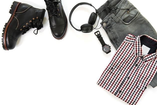 Die zufälligen ausstattungen der männer für mannkleidung mit der schwarzen stiefelette, uhr, kopfhörer, grauen jeans und hemd lokalisiert auf weißem hintergrund, draufsicht, kopienraum Premium Fotos