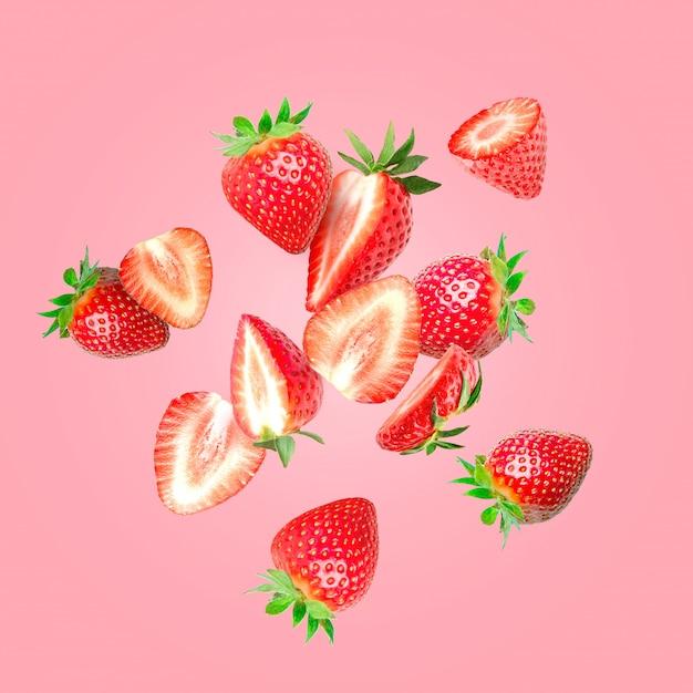 Die zusammensetzung von erdbeeren. erdbeeren in stücke schneiden, die in die luft fliegen Premium Fotos