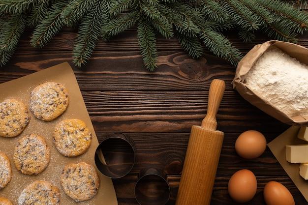 Die zutaten für die herstellung von weihnachtsplätzchen liegen auf einem holztisch Premium Fotos