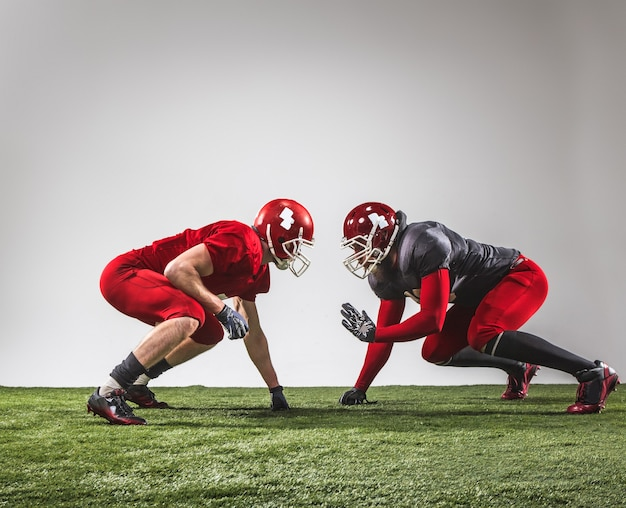 Die zwei american-football-spieler in aktion auf grünem gras und grauem hintergrund. Kostenlose Fotos