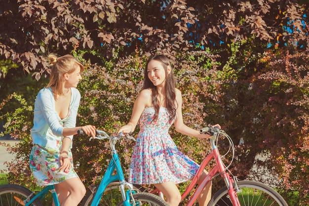 Die zwei jungen mädchen mit fahrrädern im park Kostenlose Fotos