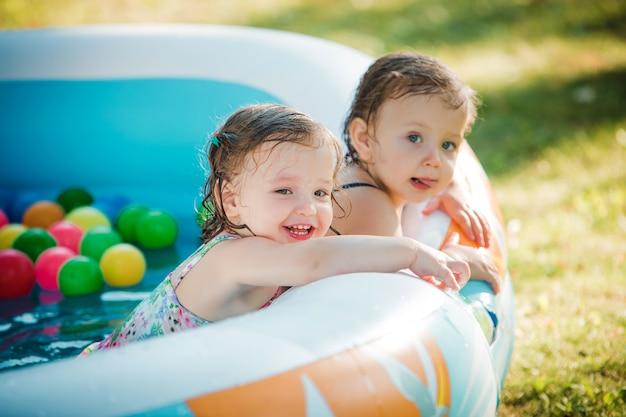Die zwei kleinen mädchen spielen mit spielzeug im aufblasbaren pool im sonnigen sommertag Kostenlose Fotos