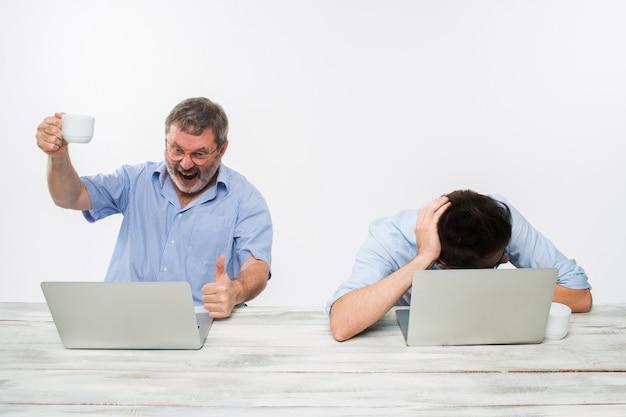 Die zwei kollegen, die im büro auf weißem hintergrund zusammenarbeiten Kostenlose Fotos