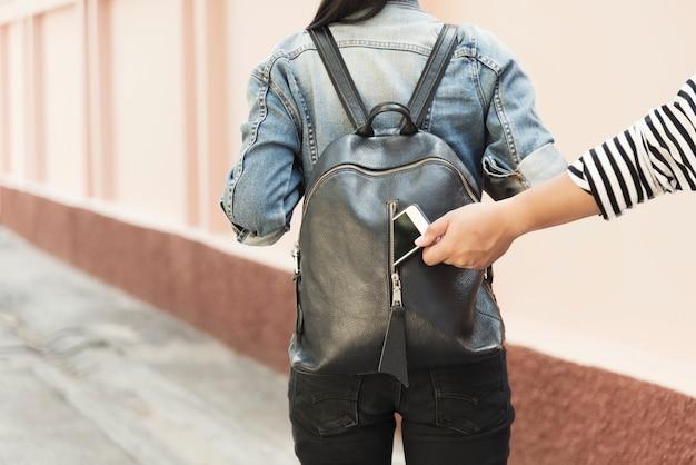 Dieb, der mobile von der reisetasche auf straße stiehlt. Premium Fotos