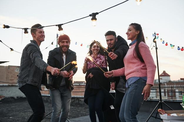 Diese leute freuen sich, zusammen zu feiern. spielen mit wunderkerzen auf dem dach. gruppe junger schöner freunde Kostenlose Fotos
