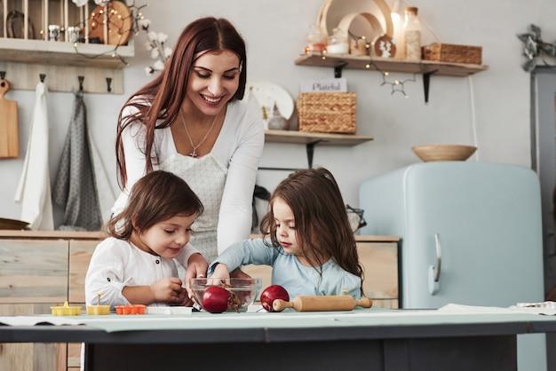 Dieses mädchen machte das essen speziell für sie. junge schöne frau geben die plätzchen, während sie nahe der tabelle mit spielwaren sitzen Premium Fotos