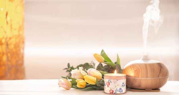 Diffusorlampe des aromatischen öls auf dem tisch auf einem unscharfen hintergrund mit einem schönen frühlingsstrauß von tulpen und brennender kerze. Kostenlose Fotos