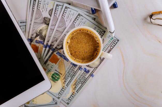Digital-tablet-computer mit dem kaufen von flugtickets in den us-dollar banknoten, mit flugzeugurlaubsreisetasse kaffee. Premium Fotos