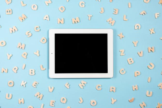 Digital-tablette mit der schwarzen bildschirmanzeige umgeben mit hölzernen buchstaben auf blauem hintergrund Kostenlose Fotos