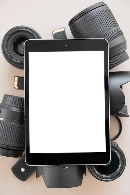 Digital-tablette mit leerem bildschirm über kameraobjektiv und zubehör über farbigem hintergrund Kostenlose Fotos