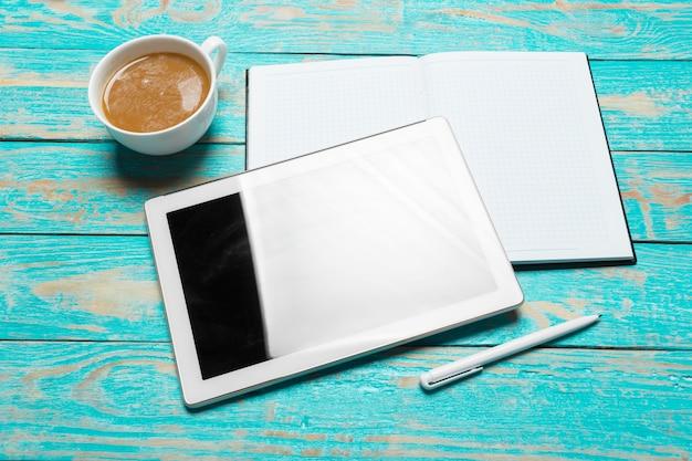 Digital-tablette und kaffeetasse auf holztisch Premium Fotos
