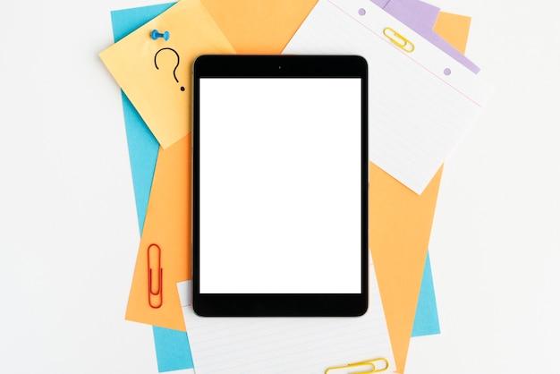 Digitale tablette des leeren bildschirms auf buntem papier und papierklammern Kostenlose Fotos