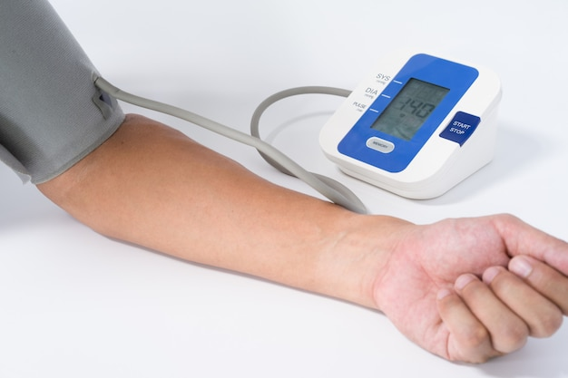 Digitales blutdruckmessgerät mit dem arm eines mannes auf weiß Premium Fotos