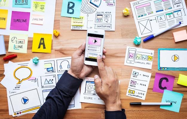 Digitales geschäftsmarketing mit papierkramskizze und männlicher hand, die smartphone auf holztisch berührt. Premium Fotos
