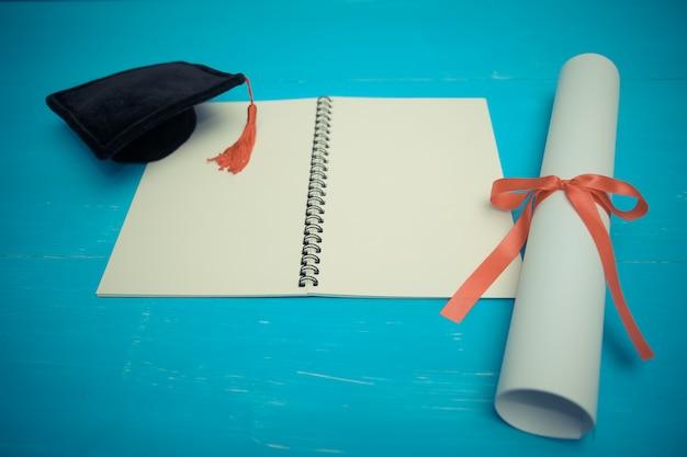 Diplom mit rotem band und schwarzer staffelungskappe auf holz Premium Fotos
