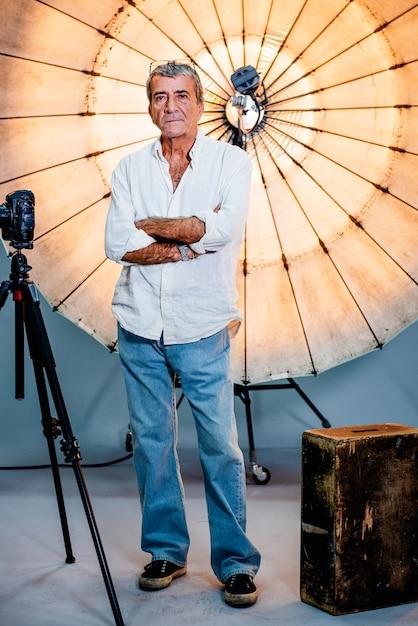 Direktor, der vor einem reflektierenden regenschirm in einem studio steht Premium Fotos