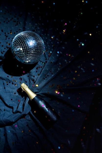 Discokugel mit champagnerflasche auf fußboden Kostenlose Fotos