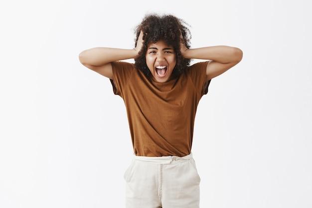 Distressed sauer sauer satt verärgert teenager-mädchen mit afro-haarschnitt schreien händchenhalten auf dem kopf unglücklich mit eltern streiten jedes mal vor negativen gefühlen über graue wand schreien, den verstand verlieren Kostenlose Fotos