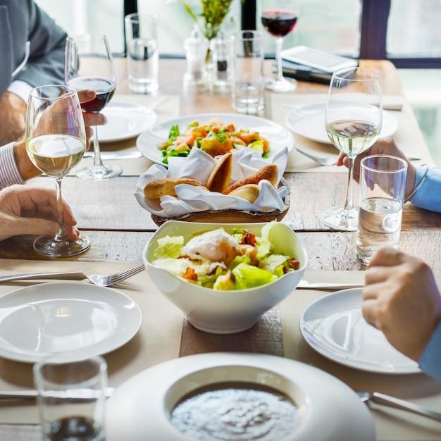 Diverse gruppe von erwachsenen essen, geselligkeit und diskutieren geschäfte Premium Fotos