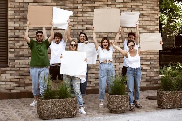 Diverse gruppe von menschen, die mit leeren zeichen protestieren. protest gegen menschenrechte, missbrauch der freiheit, soziale fragen Kostenlose Fotos
