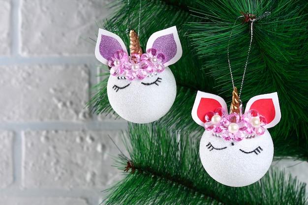 Diy, das einhorn. wie man ein einhorn aus einem weihnachtsballspielzeug herstellt. schritt für schritt führerfoto. Premium Fotos