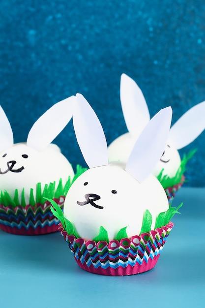 Diy-kaninchen von ostereiern auf blauem hintergrund. geschenkideen, dekor ostern, frühling. handgefertigt Premium Fotos