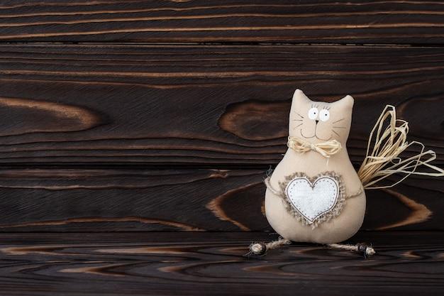 Diy, katzenspielzeug auf hölzernem hintergrund. handgemachtes kätzchen mit herz aus textil. natürliche bretter aus dunklem holz, textraum. romantische karte, liebeskonzept. vintage dekoration, kinderspielzeug. Premium Fotos