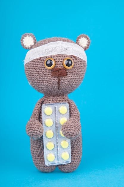 Diy spielzeug. gestricktes braunbärjunges mit tabletten. prävention von kinderkrankheiten. . Premium Fotos